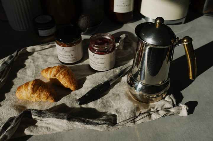 stainless steel teapot beside bread knife and bread on white table